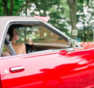 Woman in red car in wedding dress