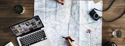 two people plan a vacation with laptop and map
